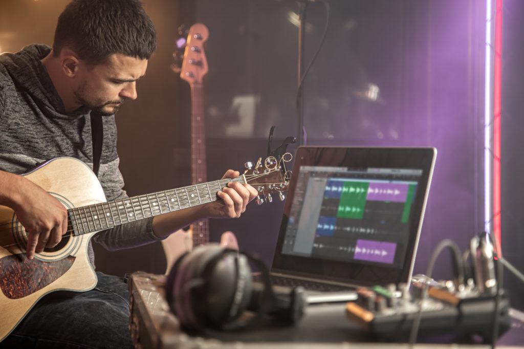 professional musician recording in studio. guitarist sitting in front laptop monitor in recording studio.